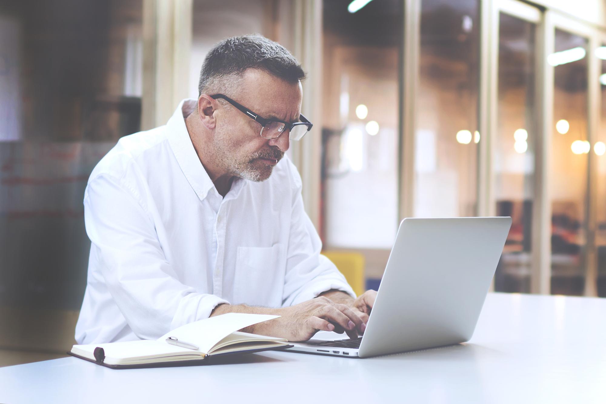 man writing blog on laptop